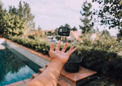 person throwing black action camera gopro teams background