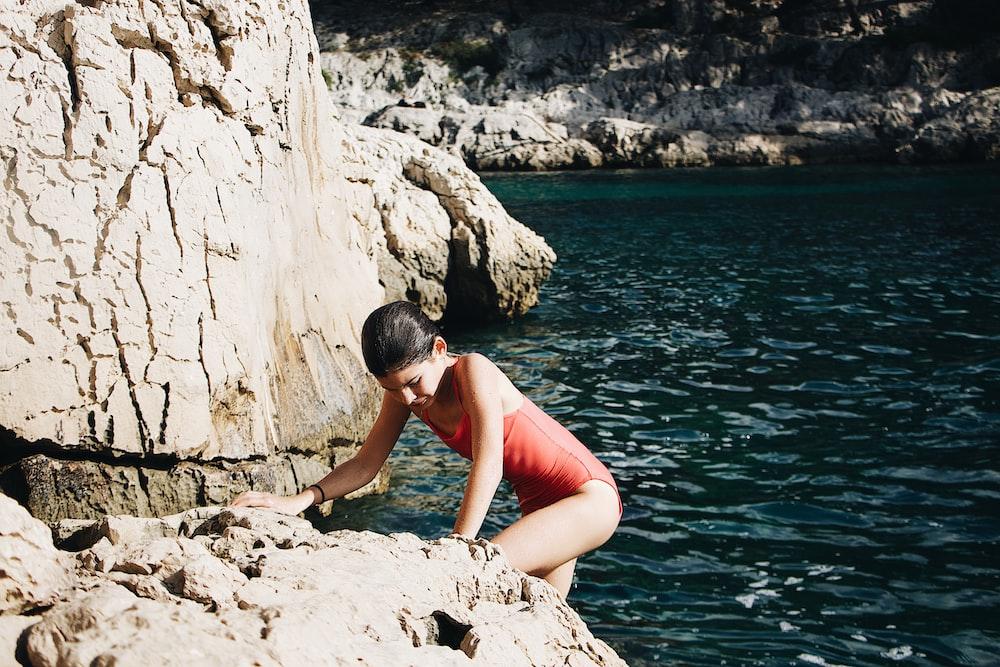 woman climbing on rock during daytime