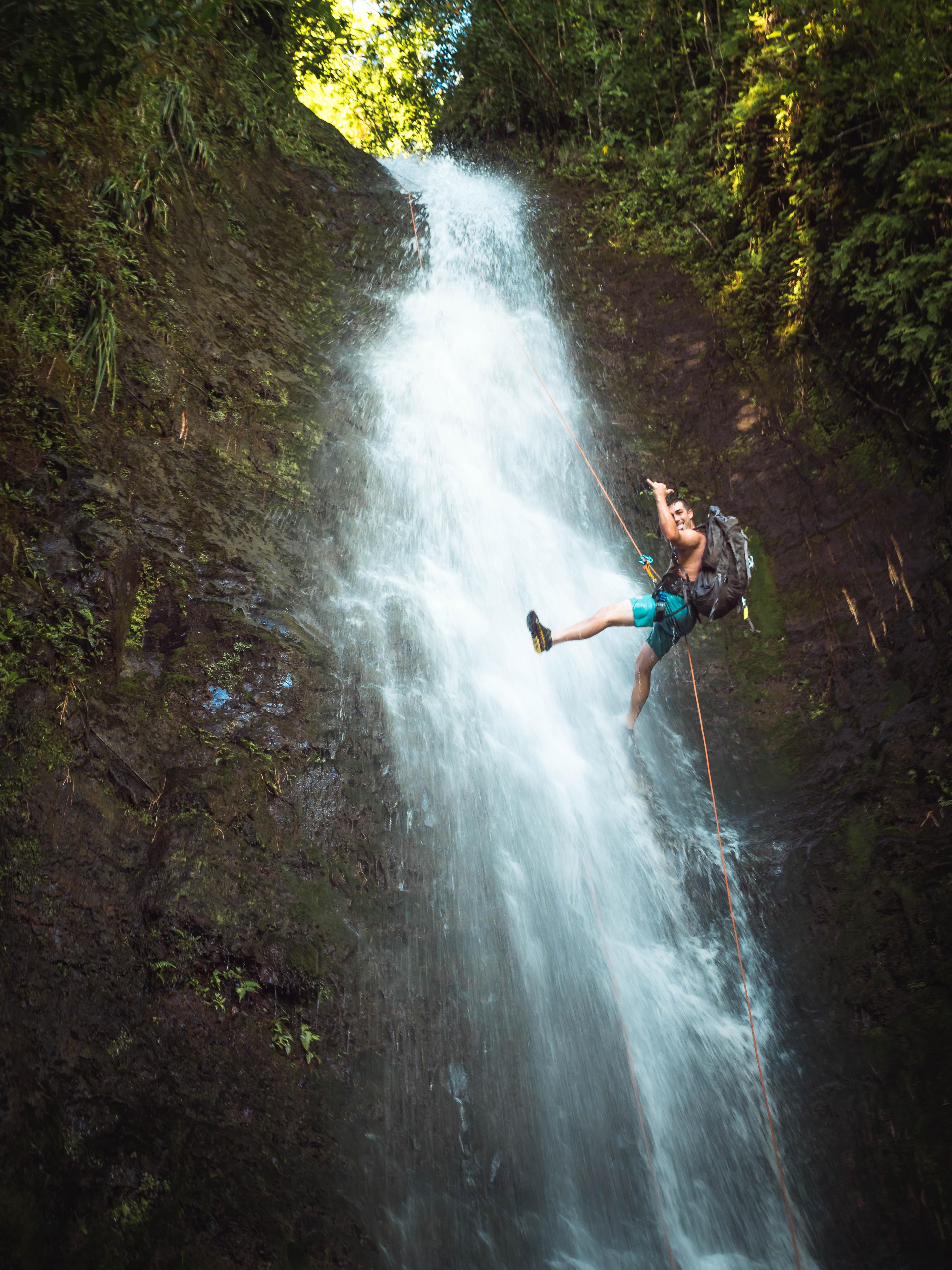 man climbing on waterfalls