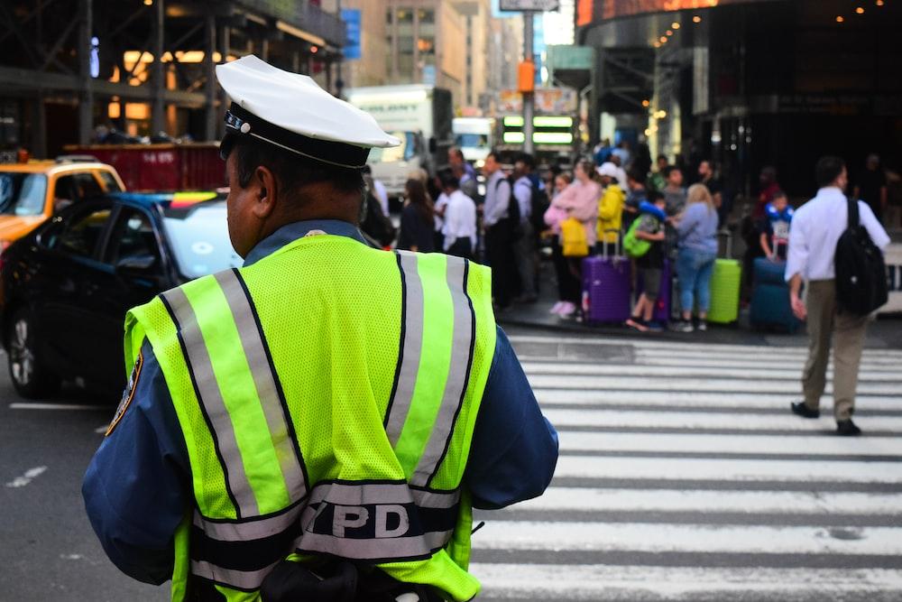 man wearing auxiliary vest standing near pedestrian lane