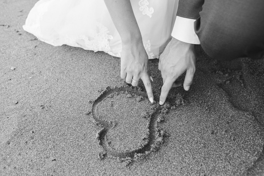 grayscale photography of man and woman draw heart on sand
