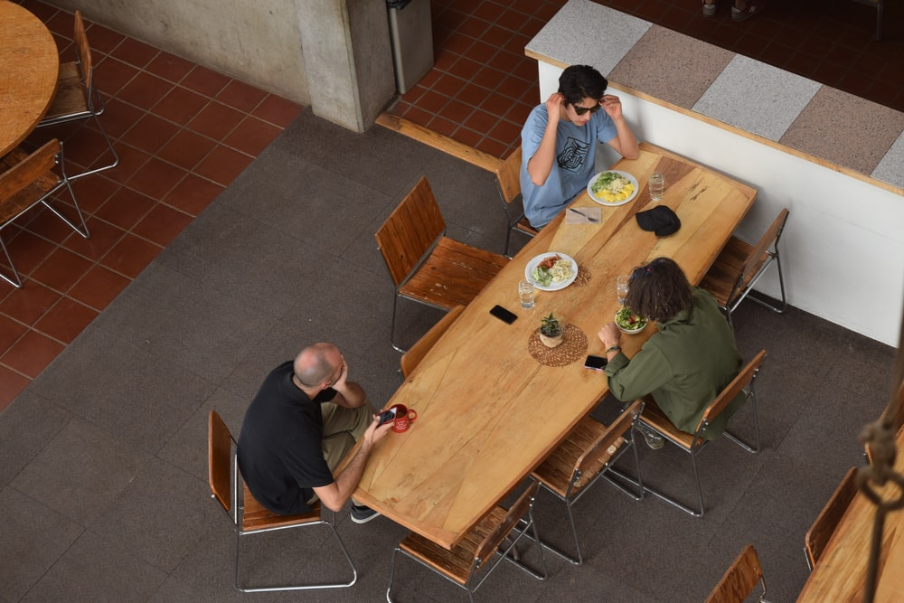 three people sitting at table in aerial shot