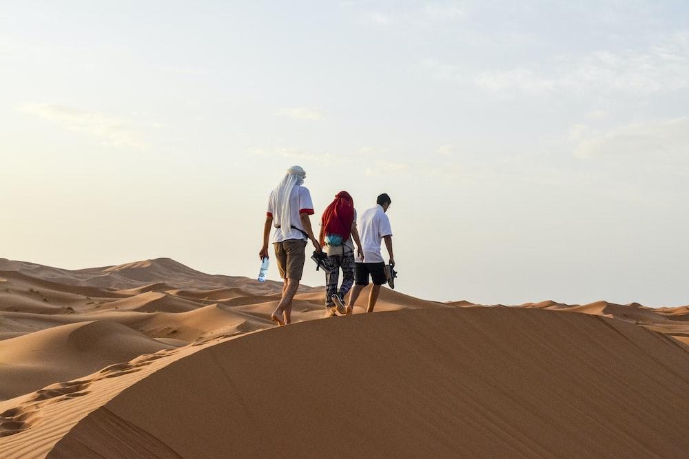 three men walking on desert during daytime
