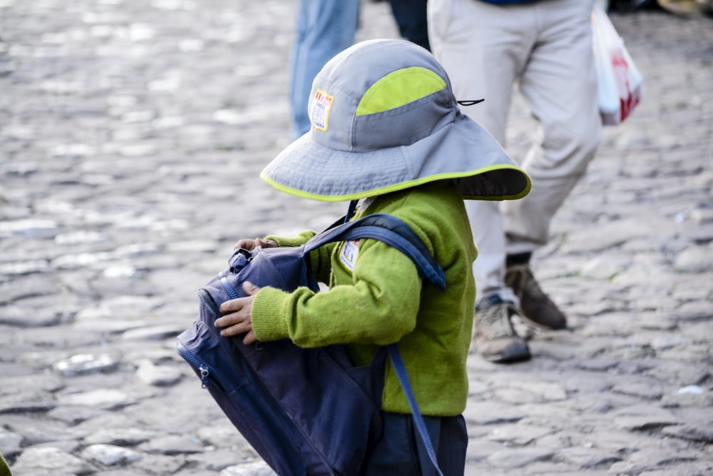 toddler carrying blue backpack