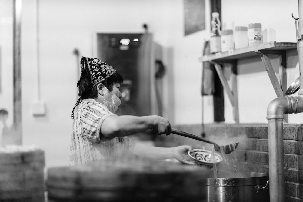 grayscale photography of woman scooping noodles