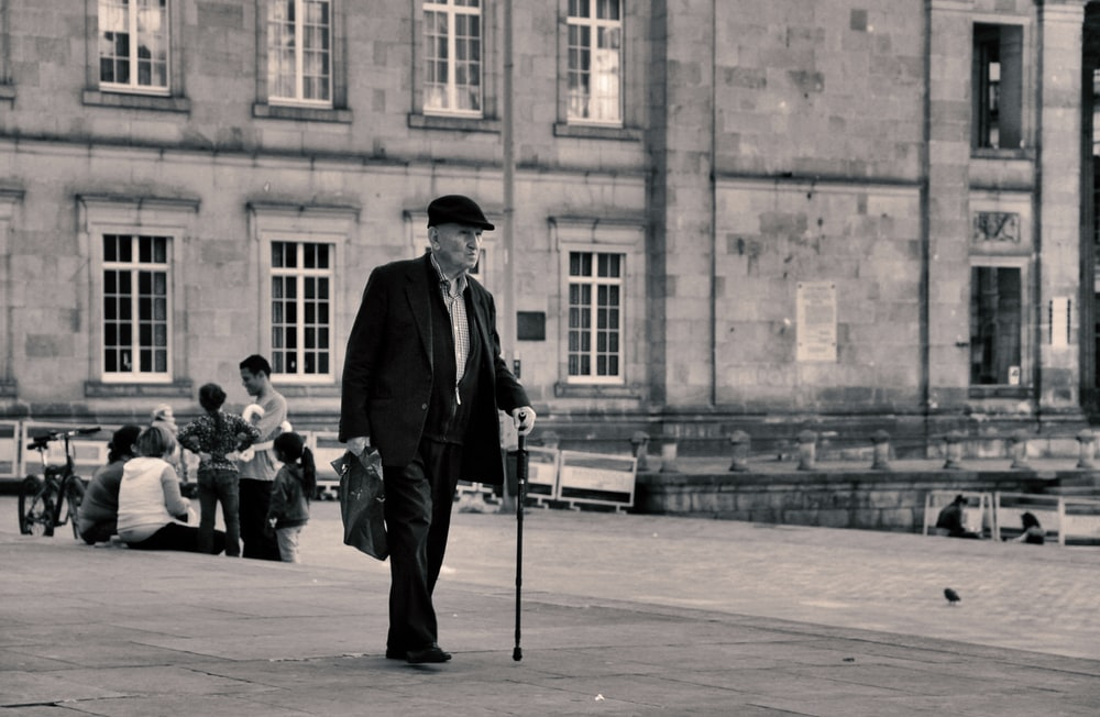 grayscale photography of man holding cane