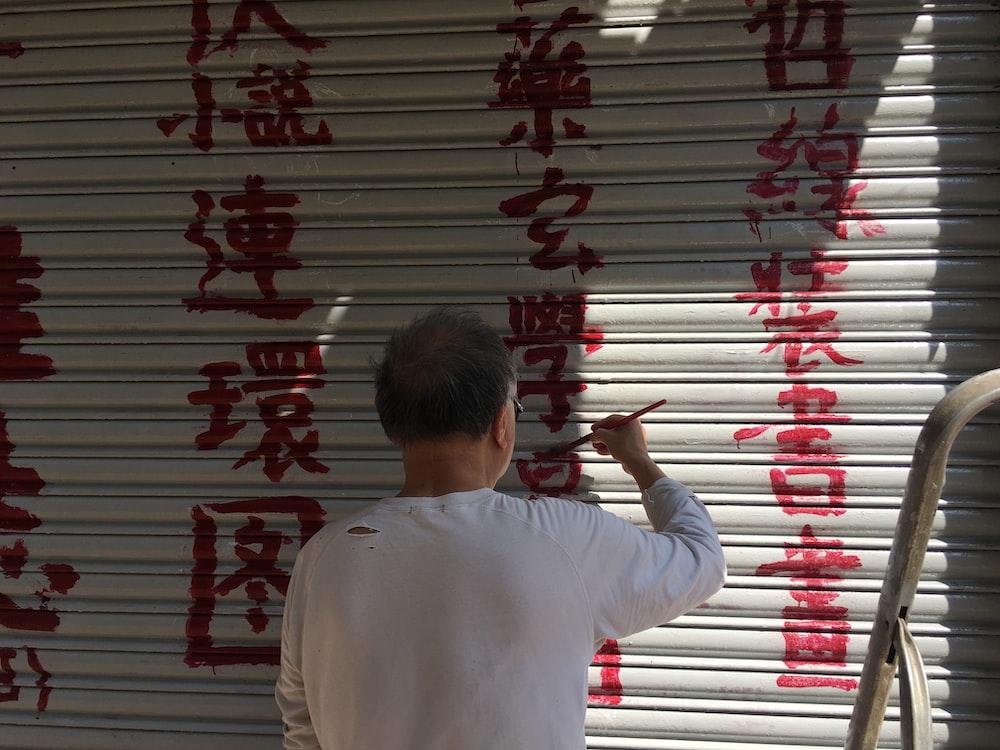 man painting Kanji text on roll-up door
