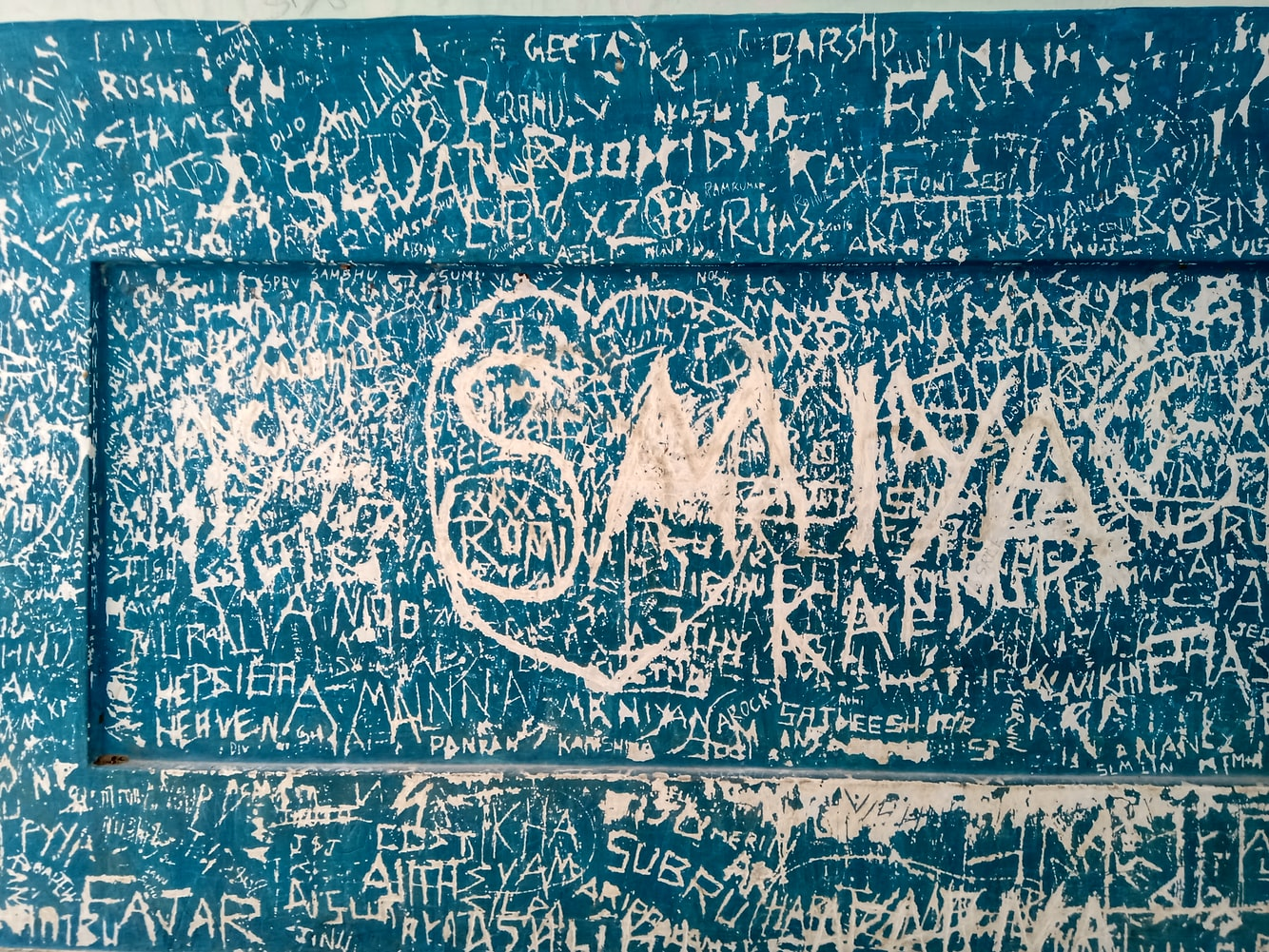 Names, phrases and shapes scratched into paint of blue wall