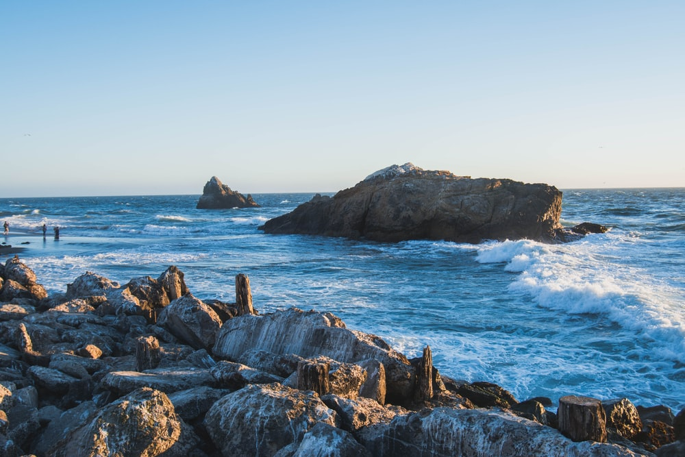 brown stone on the ocean photography