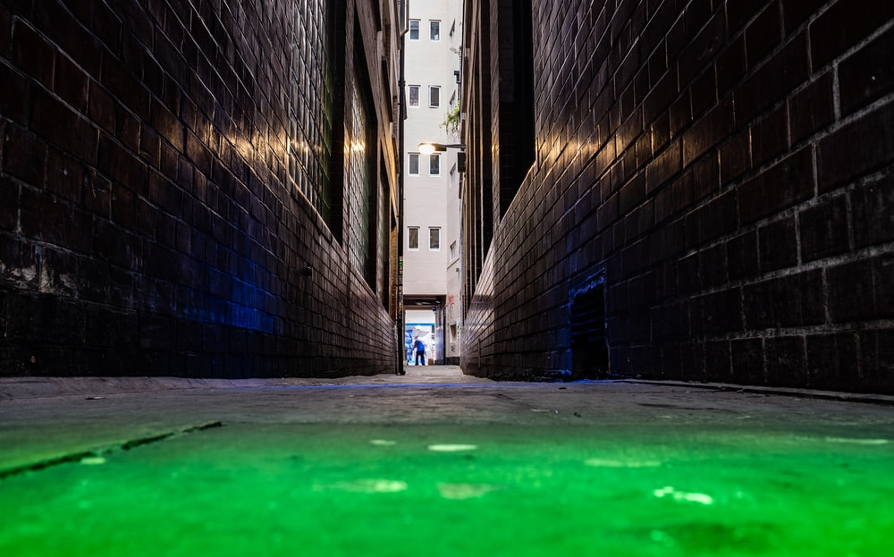 green concrete pavement between brick walls