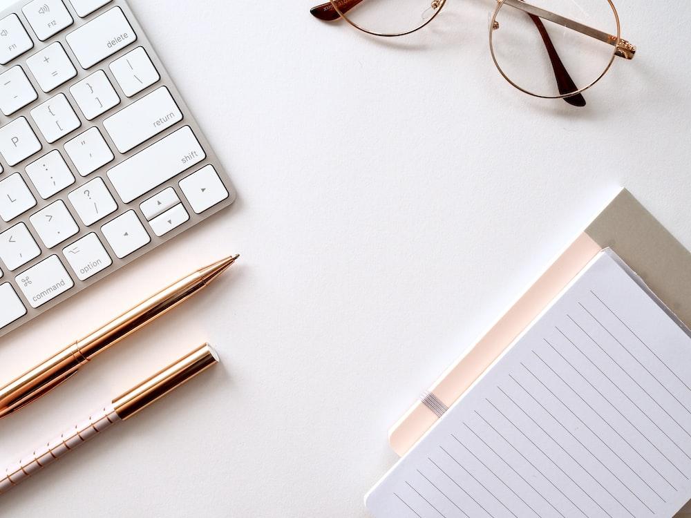 pen near black lined paper and eyeglasses