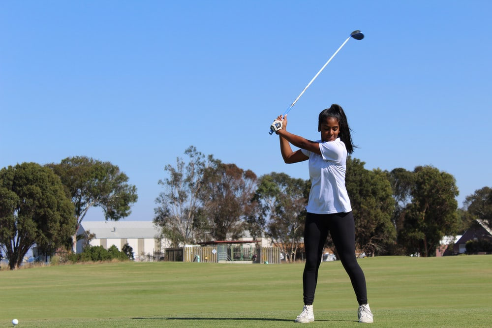 woman holding golf club during daytime