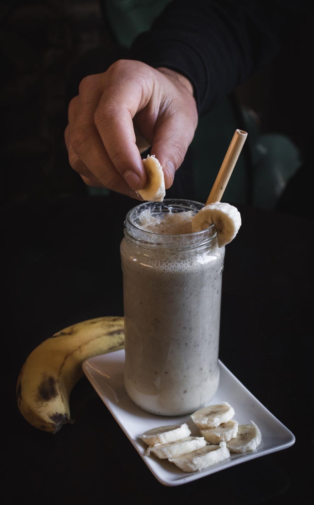 person holding slice of banana on fruit shake har