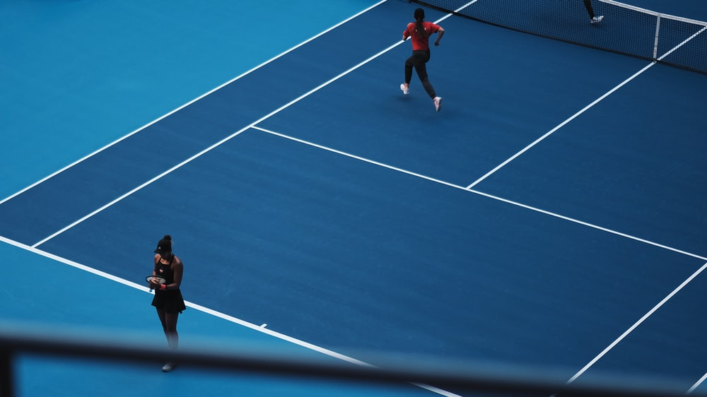 two person playing tennis during daytime