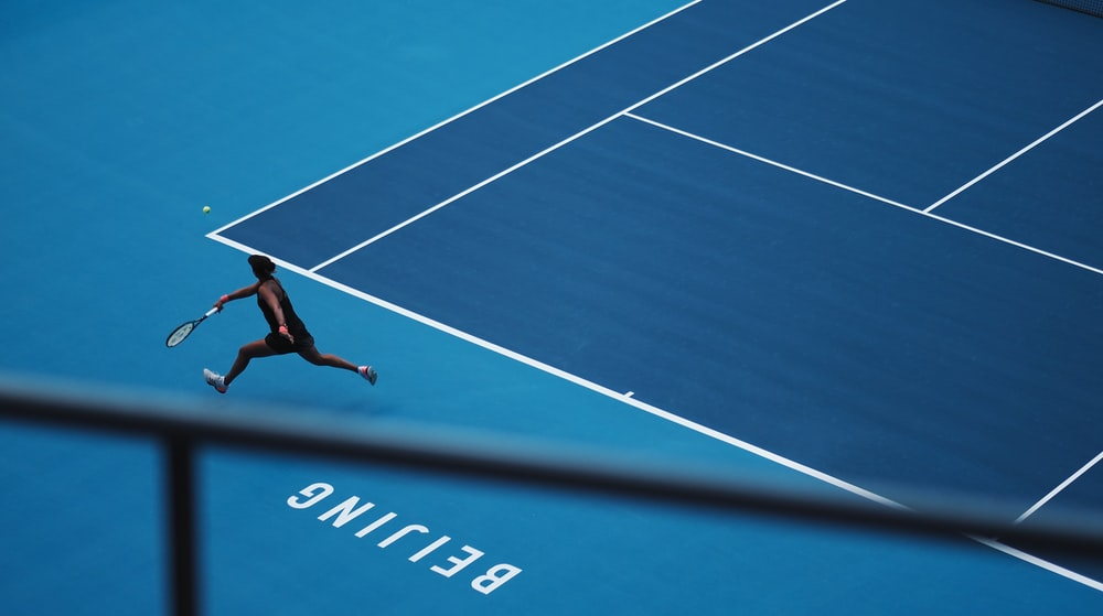 man playing tennis in court