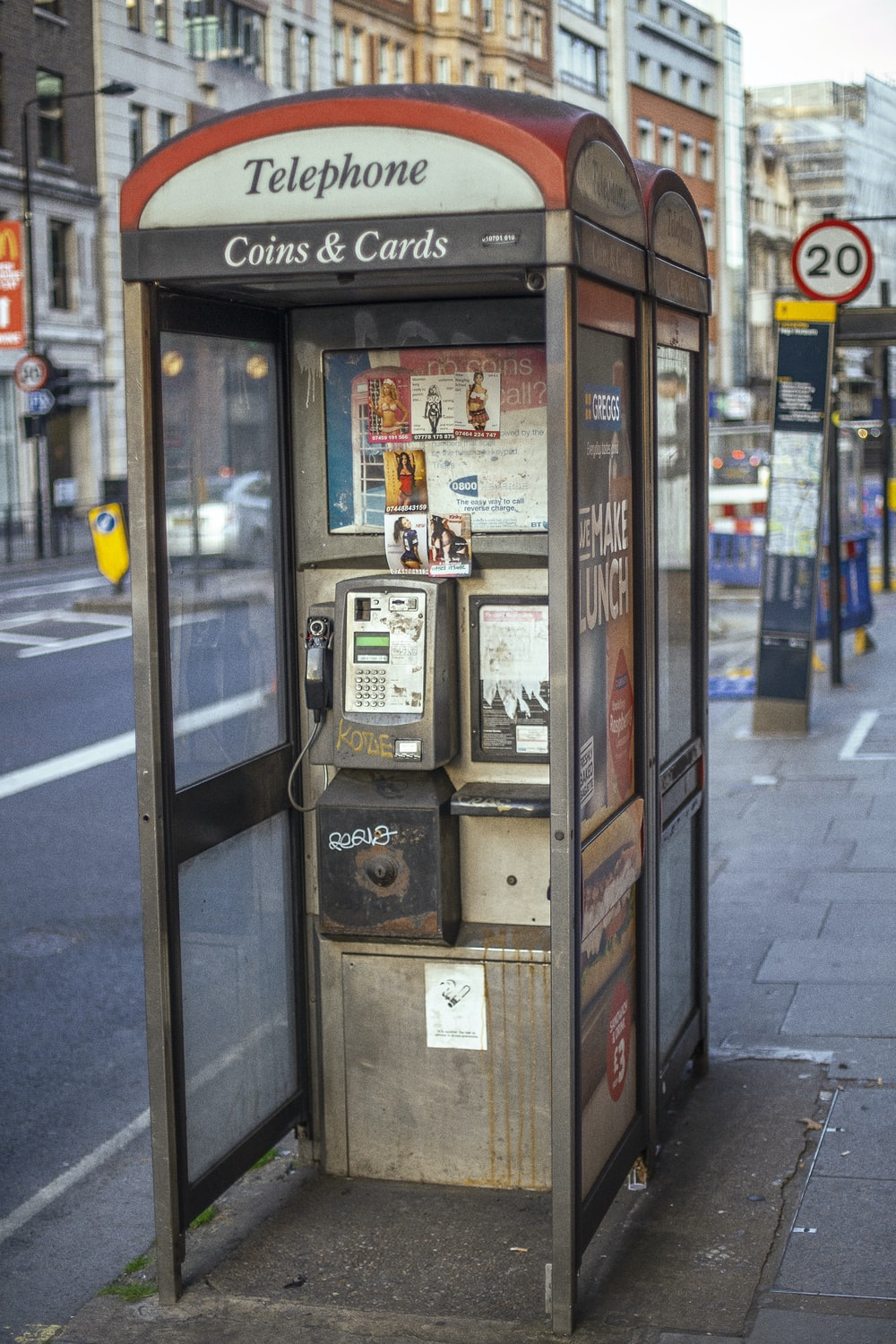 gray telephone booth along road