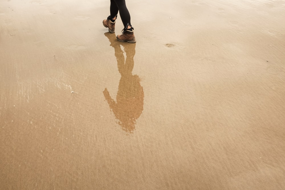 reflection of man on wet sand