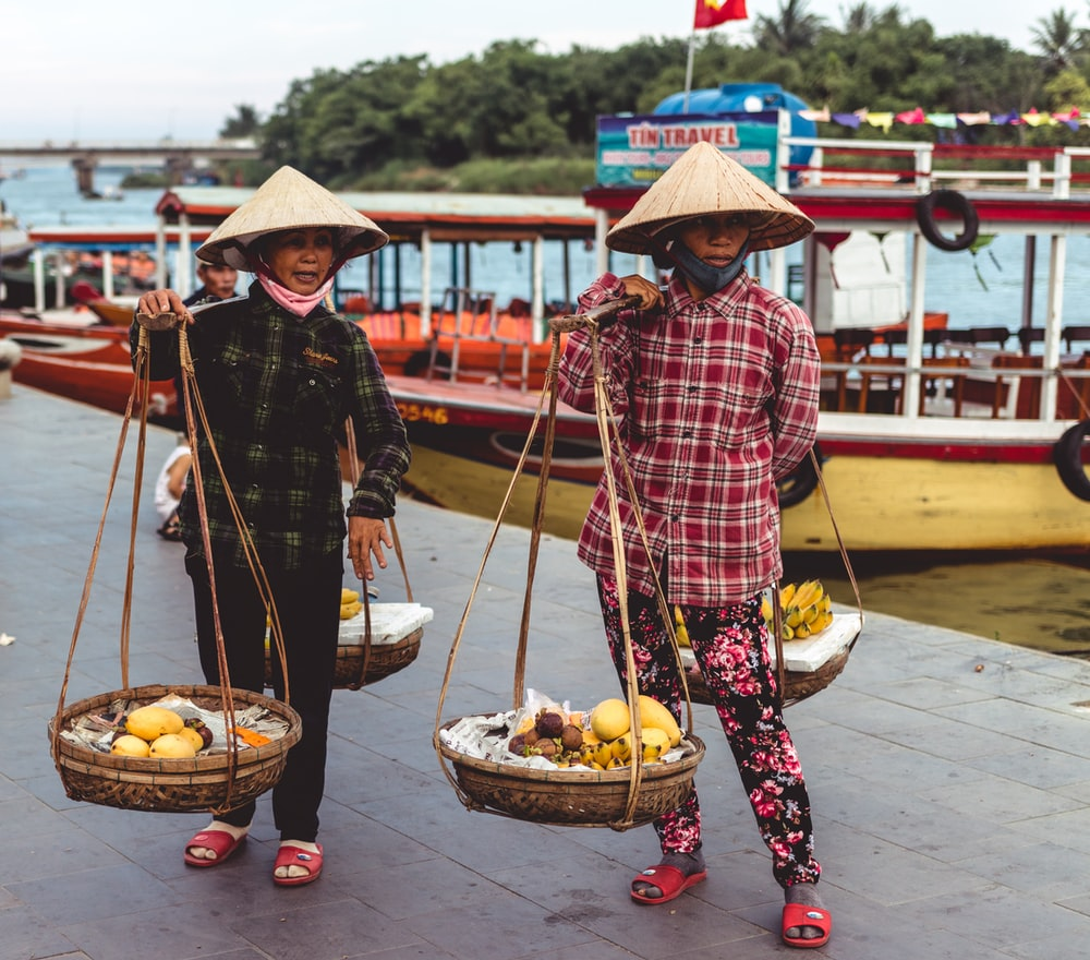 two person carrying baskets