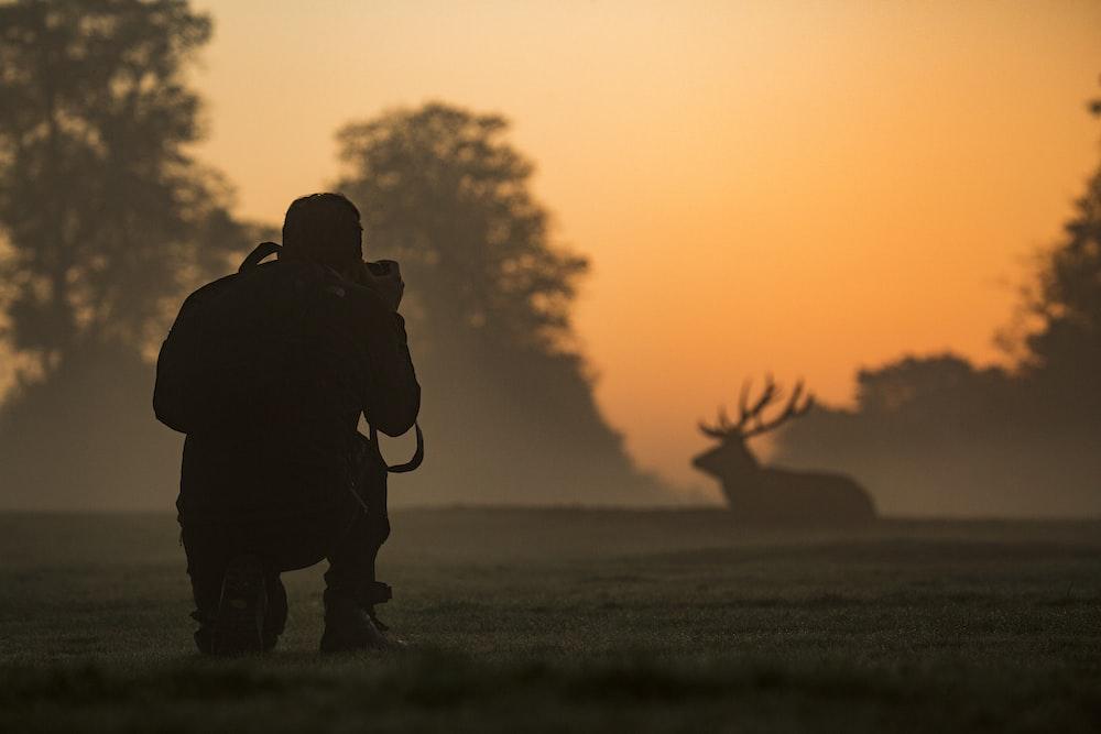 silhouette of man taking photo of deer