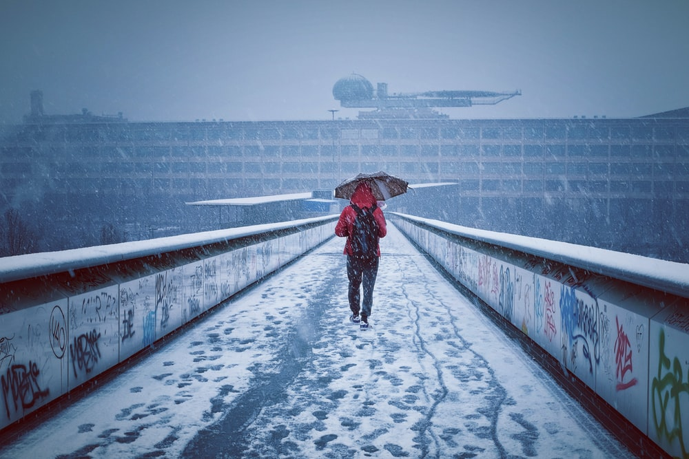 man with red hoodie and umbrella walks on snow covered pathway