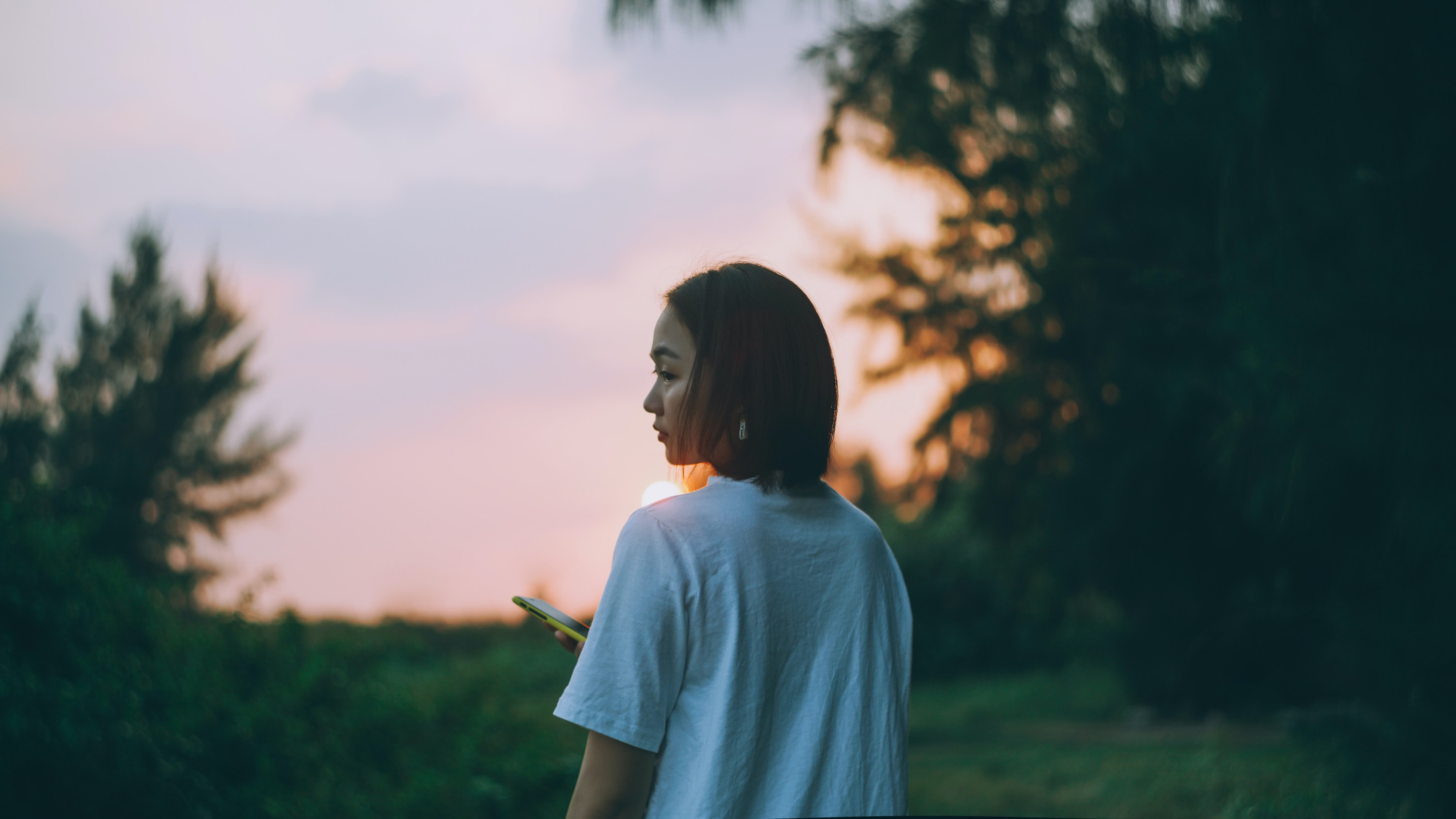 silhouette photography of woman standing near tree