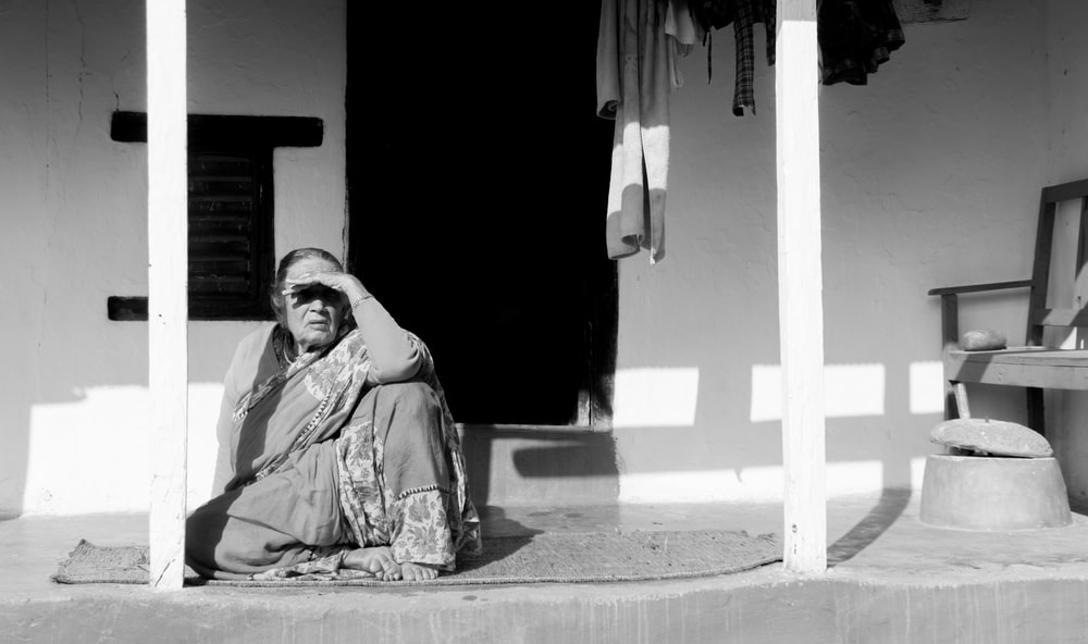 grayscale photo of woman sitting on porch