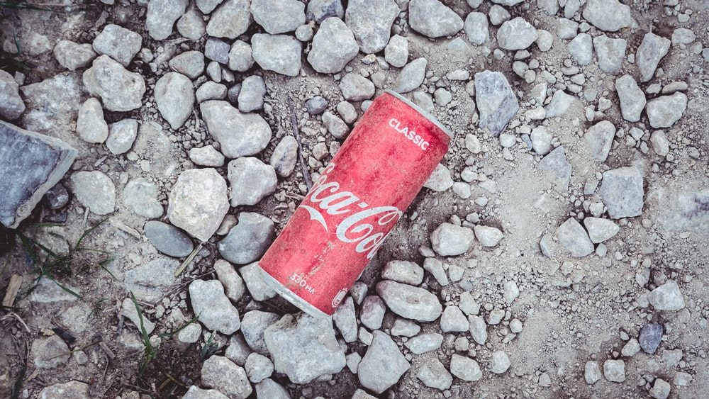 Coca Cola soda can on gray soil during daytime