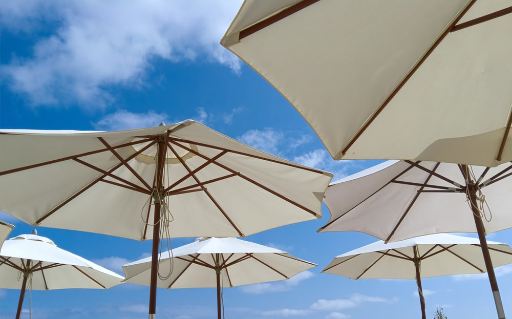 white parasols under blue and white clouds
