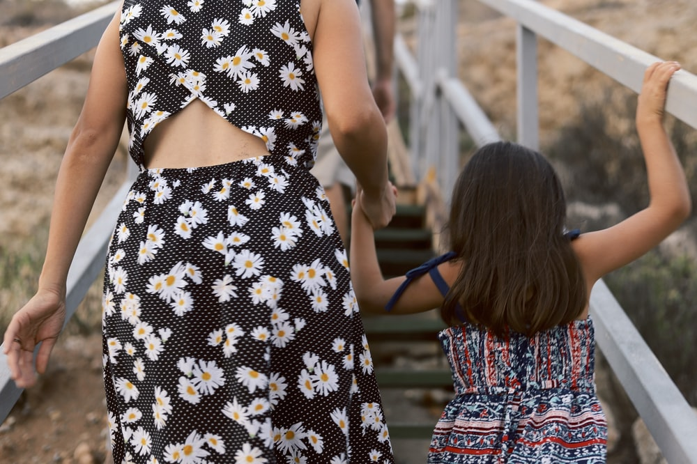 woman and girl walking on wooden stair during daytime