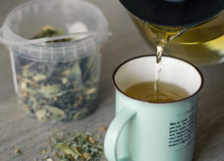 person pouring tea into white ceramic mug on top of table beside herbs at daytime