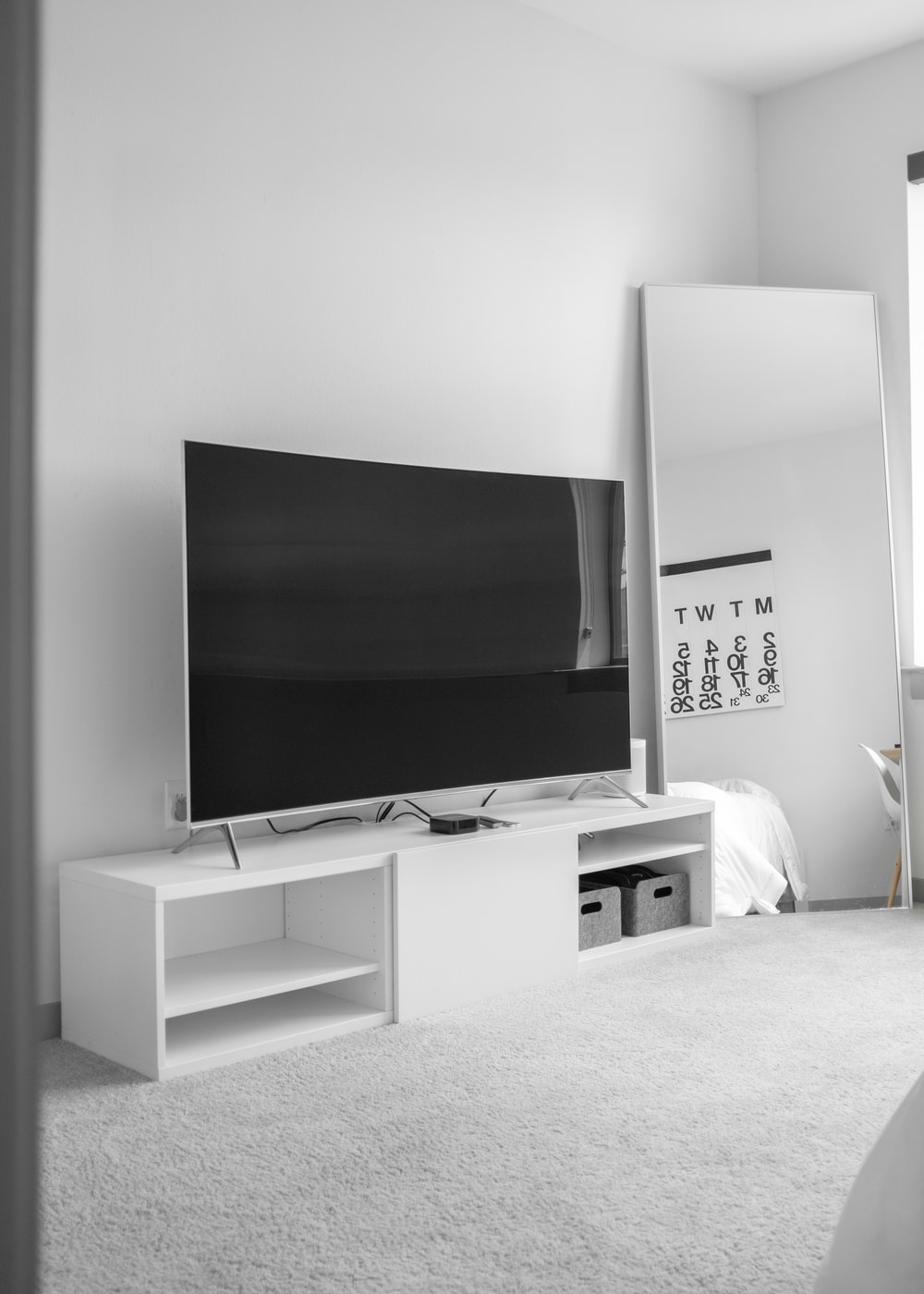 gray flat screen TV on white TV stand