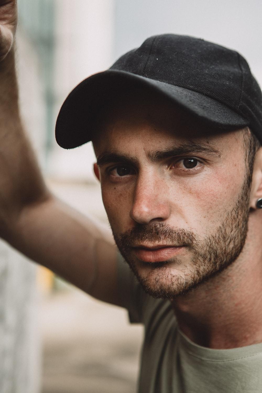 man in grey t-shirt wearing black cap