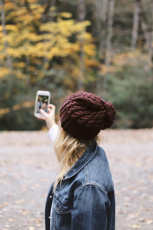 woman taking selfie near trees