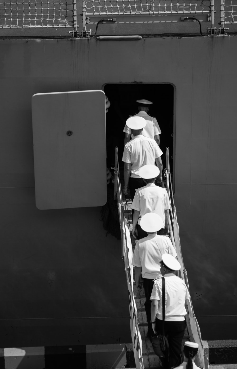 people in uniform climbing on plane stairs in grayscale photography