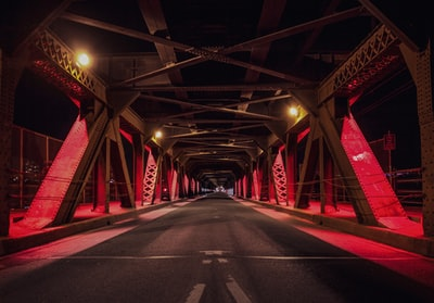 red and black metal bridge during nighttime road teams background