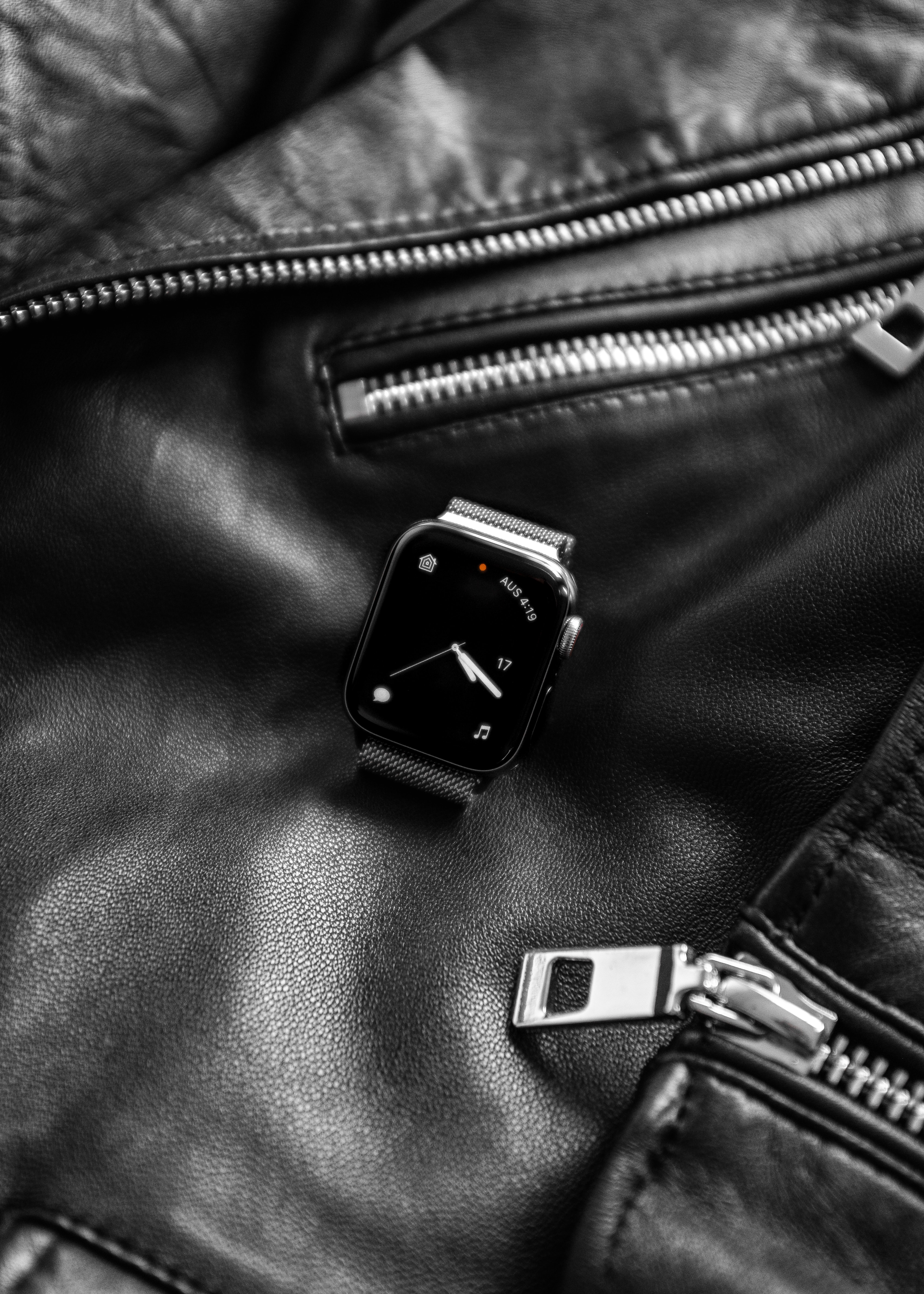black smartwatch on top of black leather jacket