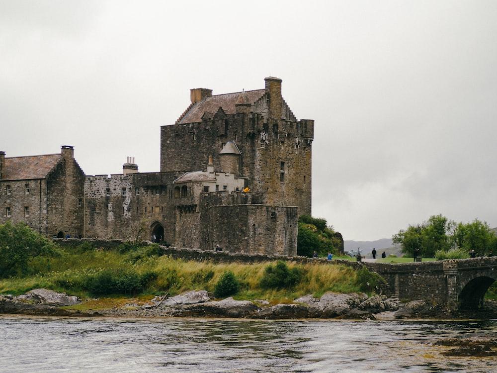 castle and bridge near body of water
