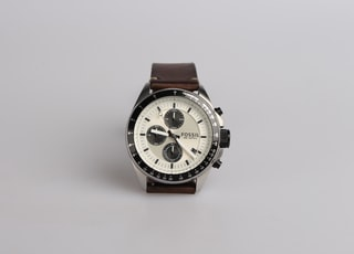 round silver-colored Fossil chronograph watch at 9:22 with brown leather band