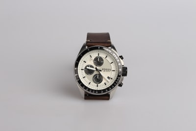 round silver-colored fossil chronograph watch at 9:22 with brown leather band watch zoom background