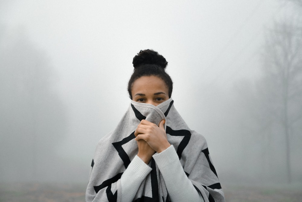 woman covering her face with fog