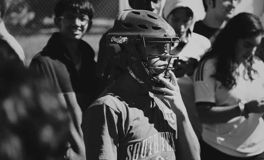 grayscale photo of man wearing catchers helmet