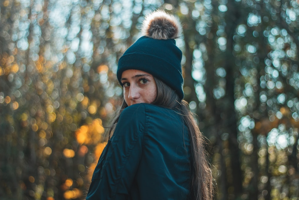 woman in bobble hat and black jacket