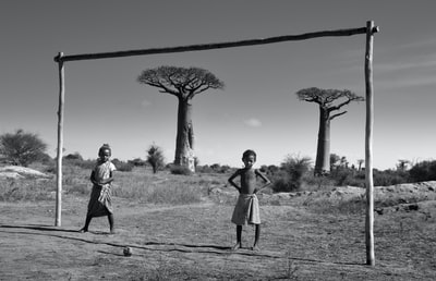 grayscale photo of two children near wood frame madagascar teams background