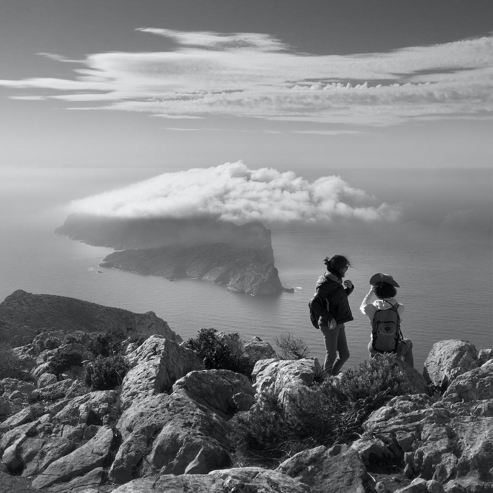 grayscale photo of two women on rock beside sea