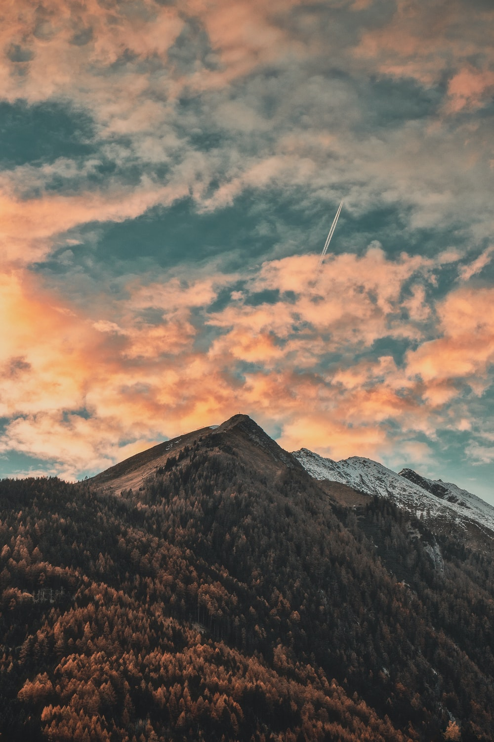 mountain top under grey and orange clouds