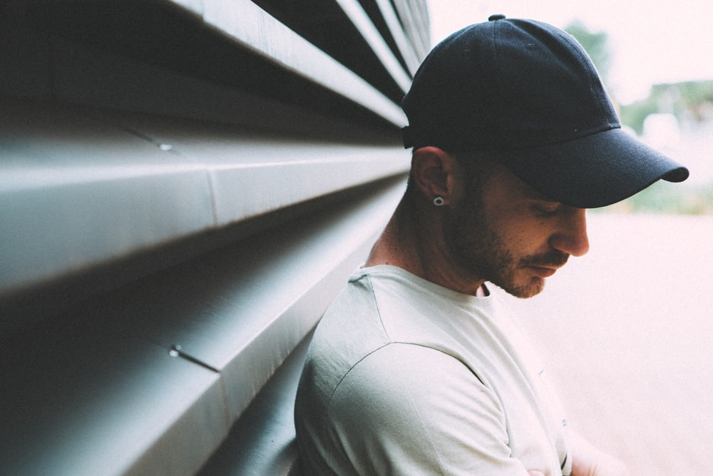 man wearing black cap and white shirt leaning on gray metal wall