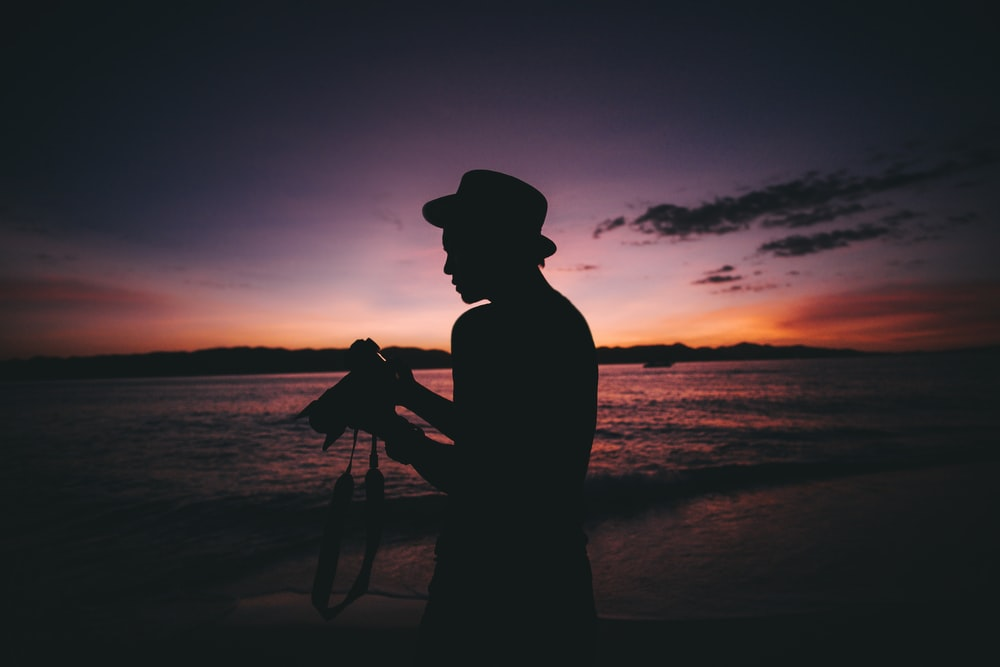 silhouette photography of man standing while holding DSLR camera