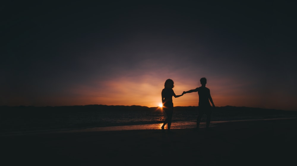 silhouette photo of couple beside sea