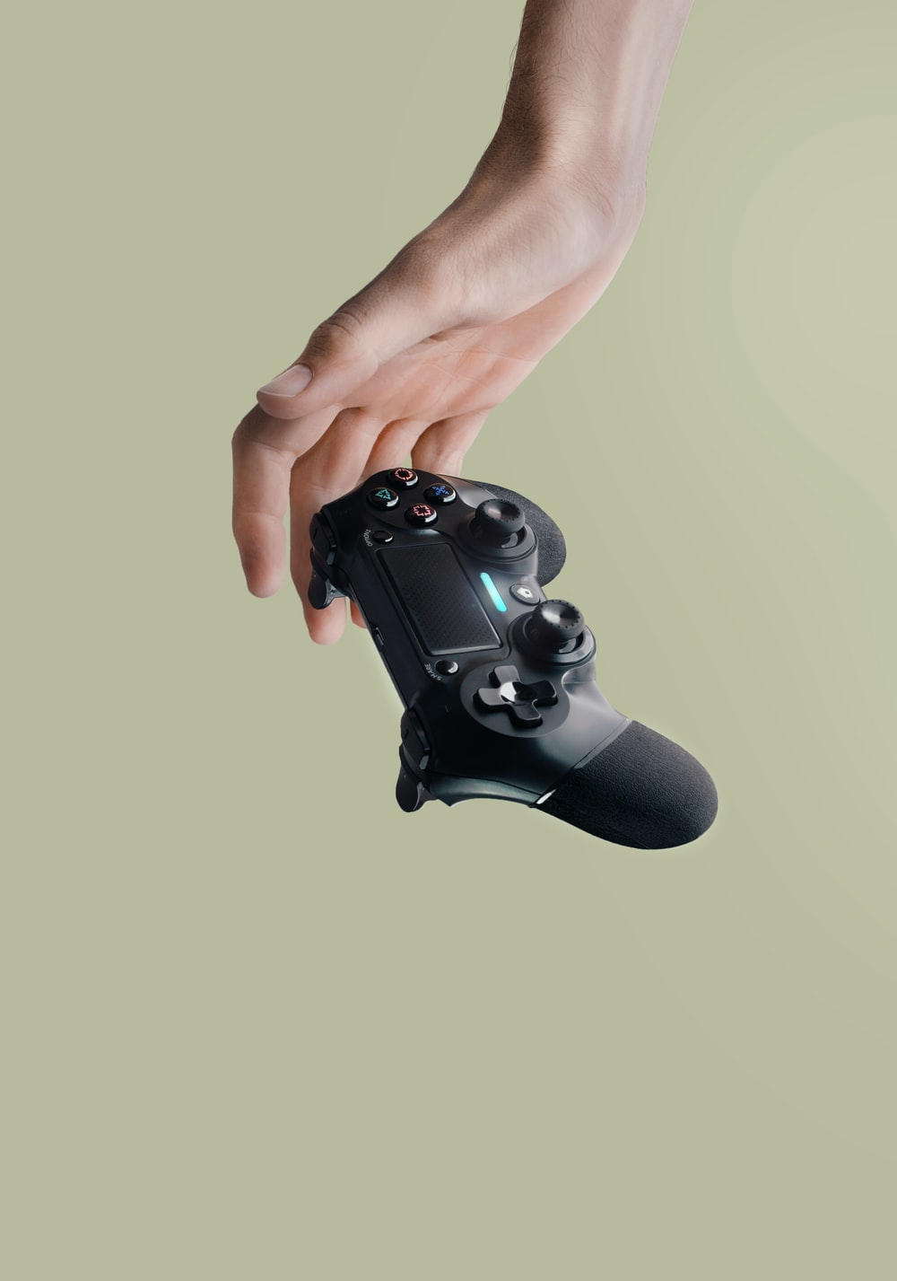 person holding Sony DualShock 4 wireless controller
