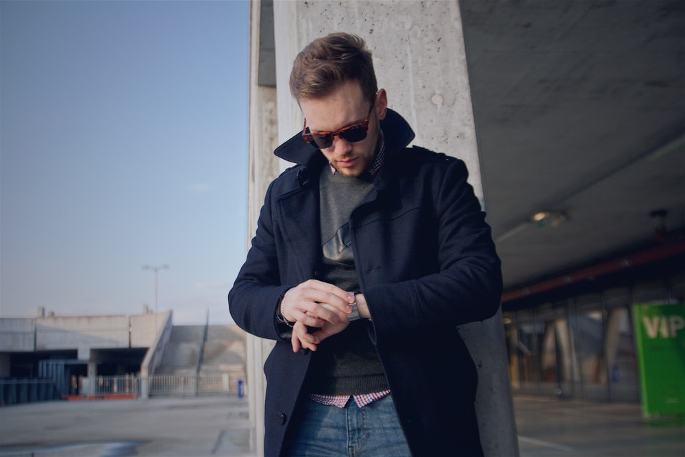 man wearing black coat looking at watch